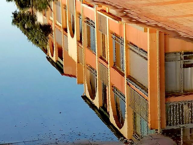 Immeuble se reflétant dans une flaque