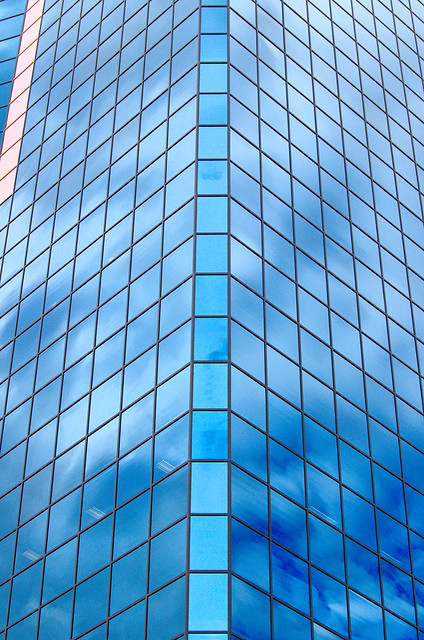 Glass office building with clouds reflected on it