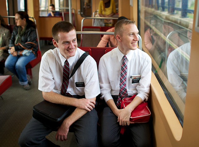 A pair of white twenty-something young men sitting on a bench seat in a bus or train; each is wearing a white shirt with a tie and a black plastic nametag