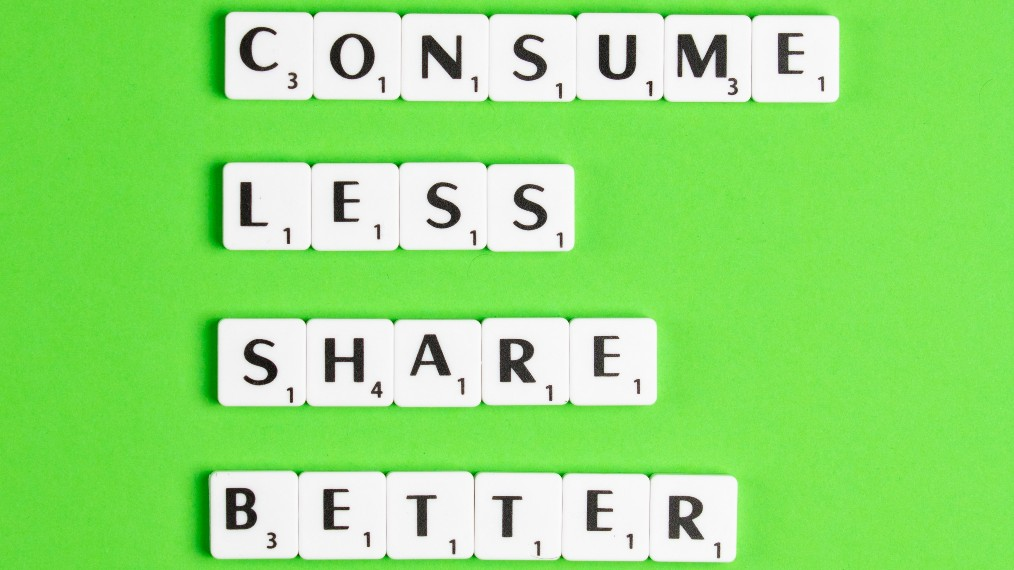 A green background, with scrabble tiles spelling out 'Consume Less, Share Better'