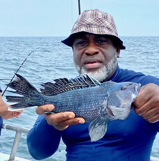 Photo of a man on a boat holding a black sea bass