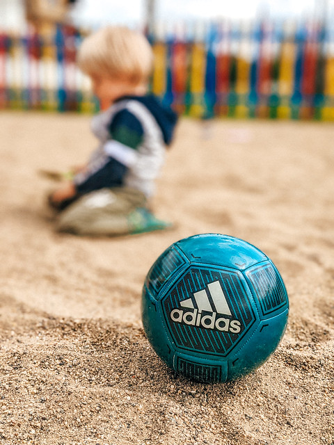 Close-up of the blue Adidas ball at sand playground with young boy in a blurry background