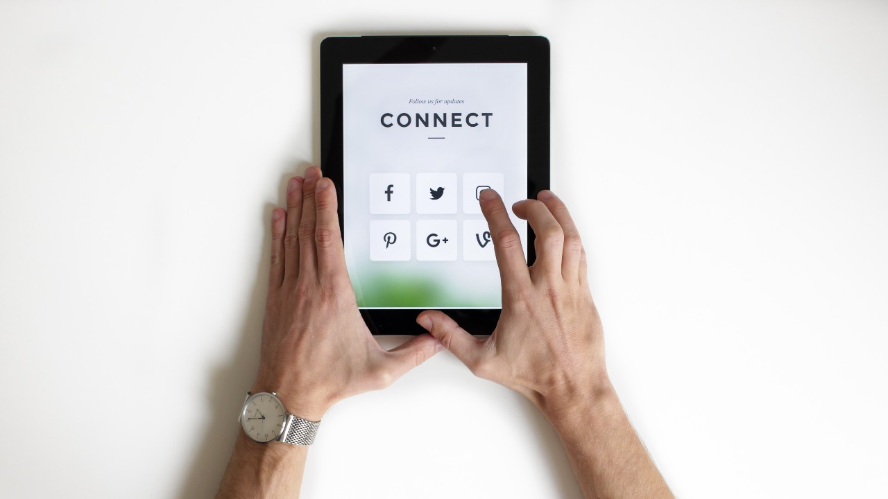 Someone holding a tablet, with different social media icons and the word 'Connect' above them