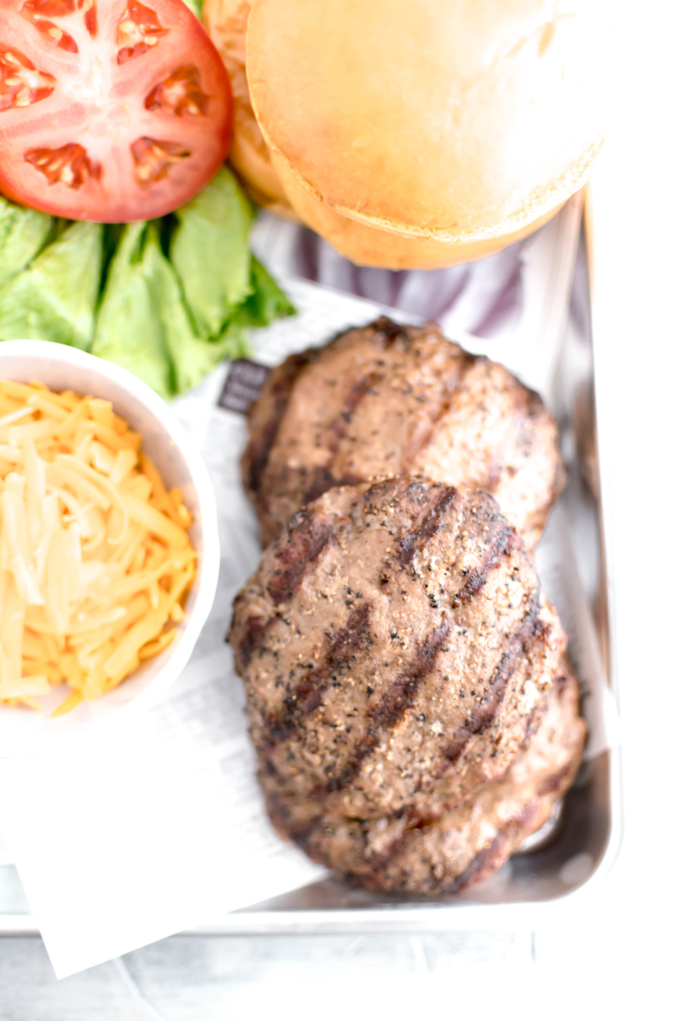 Grilled turkey burger patties on a tray with shredded cheese, lettuce, tomato and buns alongside it.