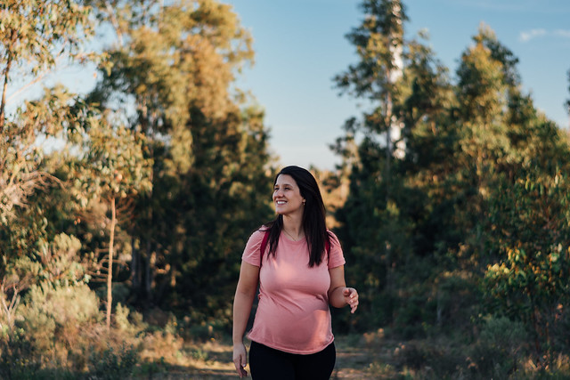 Smiling pregnant Latina woman walking in the middle of nature on a sunny day. Concept of good health and sport during pregnancy.