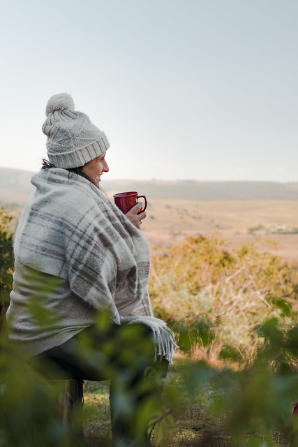 Latin woman sitting on a rustic chair, wearing a warm hat and scarf, drinking coffee while contemplating the landscape and smiling on a cold morning or afternoon. Vertical shot.