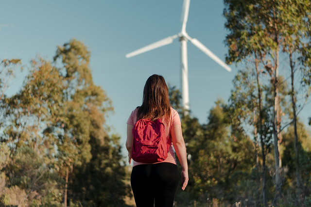 Horizontal shot of a Hispanic woman with a red backpack, walking in the middle of nature, moving towards a windmill. Concept of good health and recreational sport.