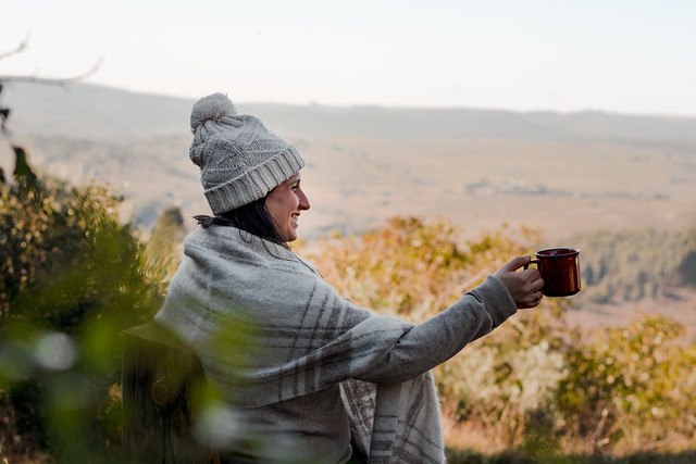 Latina woman seated in a rustic chair, with one arm outstretched and a cup in her hand. Enjoying the scenery of some hills on a cold afternoon.