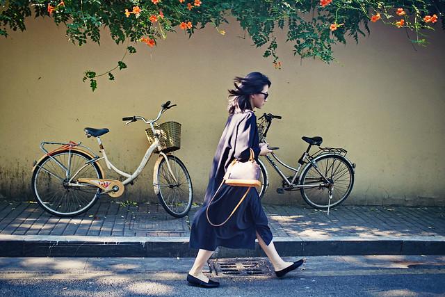 A girl walking pass campsis grandiflora