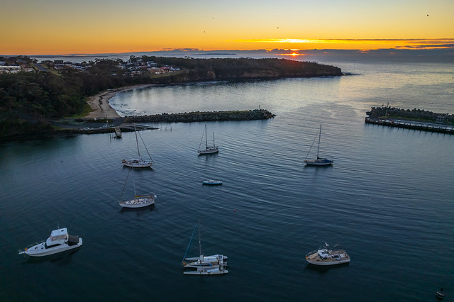 Sunrise over the harbour with low cloud bank and boats