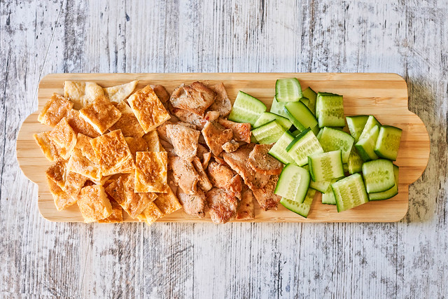 Cucumber, chicken meat and egg omelet cuts on wooden plate