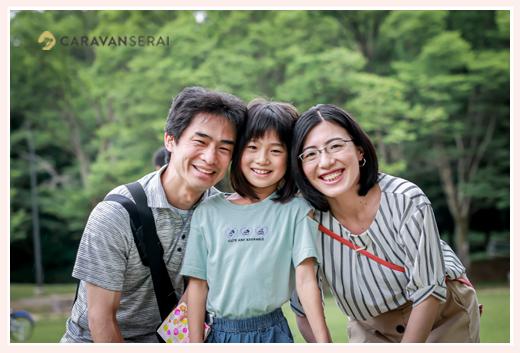 緑をバックに親子3人の写真 笑顔 公園