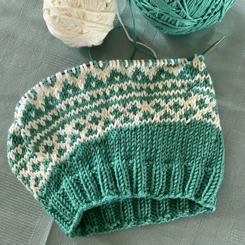 The yoke of a green and off-white colorwork baby sweater in progress, with two balls of yarn on a sage green background