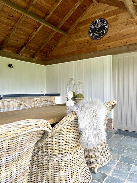 Houten Overkapping met Belgische dallen vloer rieten tuinstoelen grote klok