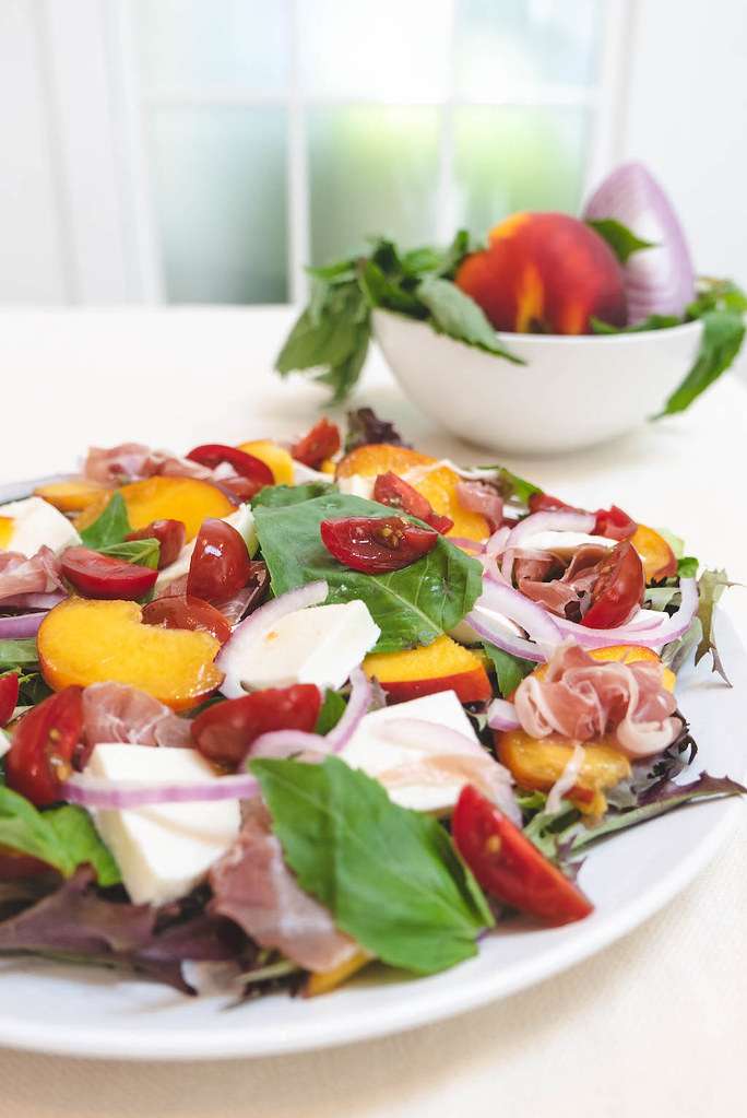 All the ingredients of the peach Caprese salad on a plate--spring mix, basil, cheese, peaches, red onions, tomatoes, and prosciutto.