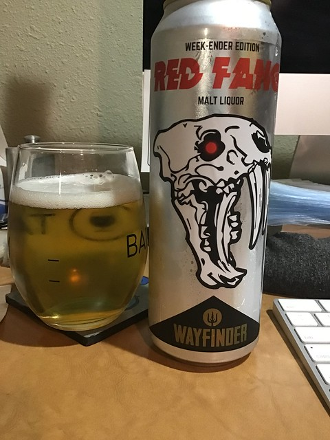 Wayfinder Red Fang malt liquor in glass next to can.