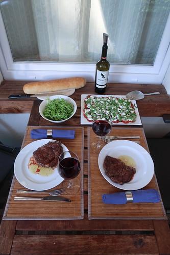 Entrecôte mit frisch gebackenem Ciabatta, grünem Salat und Mozzarella-Tomaten aus San-Marzano-Tomaten (Tischbild)