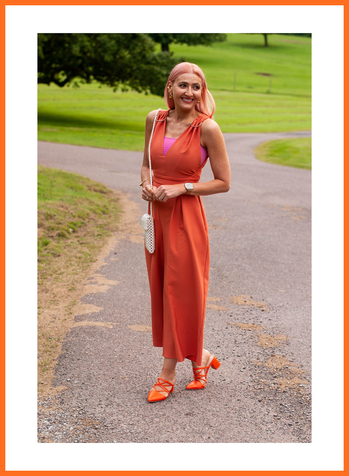 What to Wear to a Wedding Evening Reception: Orange v-neck jumpsuit, orange strappy heels, pearl phone holder   Catherine Summers, AKA Not Dressed As Lamb, Over 40 Fashion & Style