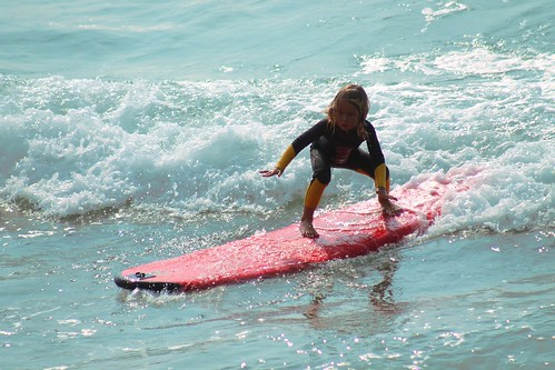 Small child surfing. From Heading to the Beach? Your Indispensable Packing List