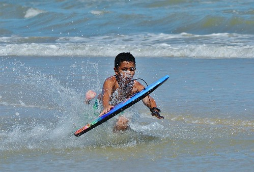 Kid in the water on a boogie board. From Heading to the Beach? Your Indispensable Packing List