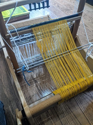 Erica small table loom viewed from the back beam with threads in a cross held by metal loom rods and spread in the black built-in raddle to set-up for weaving.  The threads are a gold cotton, and the loom is on an oak floor.  Two weaving books can be seen bracing the warp for winding-on.