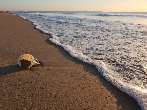 Used plastic cup in the sand on the beach. From Heading to the Beach? Your Indispensable Packing List