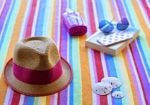 Striped beach towel with hat and book. From Heading to the Beach? Your Indispensable Packing List