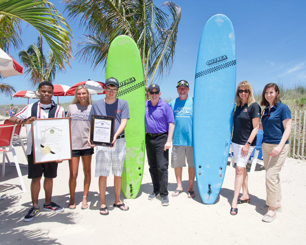 Photo of people holding surfboards on a beach