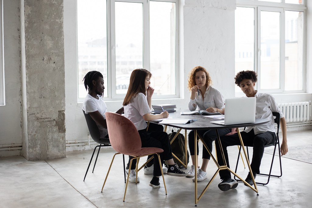 A corporate meeting setting, four people sitting around the table