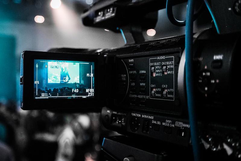 A video camera in filming mode, dark background.