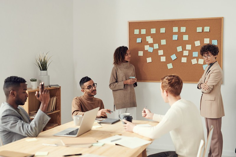 A corporate planning meeting, three people sitting at the desk, two standing next to a board of stickers.