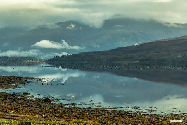 Low cloud and mist clings to the heights of Ben Nevis and is reflected in the still tidal waters of Loch Eil, Lochaber, Inverness-shire, Scotland.