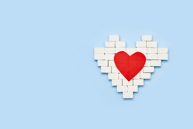 Heart shape made of sugar cubes and red heart paper cut on blue background