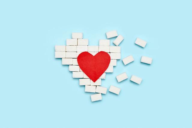Broken heart made of sugar cubes on blue background