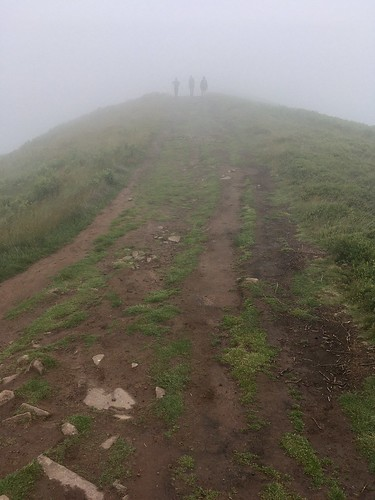Photo of a path along the ridge of Skirrid, with three people in the distance only just visible through the low clouds