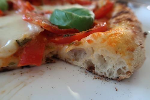 Pizza mit frischer Paprika, italienischer Salami, Mozzarella und Basilikum (angeschnitten)