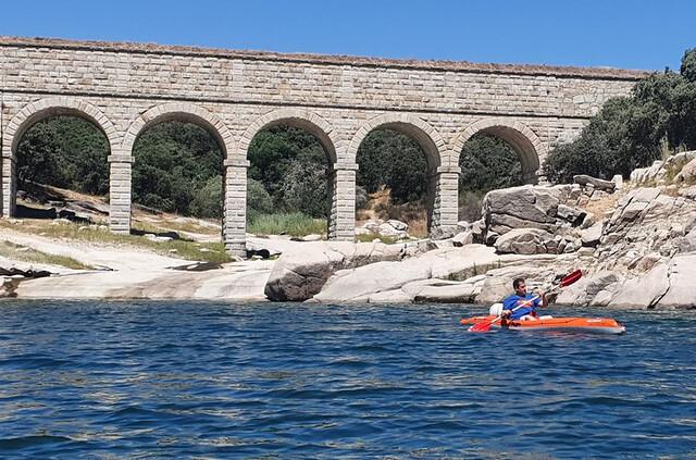 Sele haciendo kayak en el embalse de El Atazar hasta la presa de El Villar. Al fondo se aprecia el acueducto de La Alameda