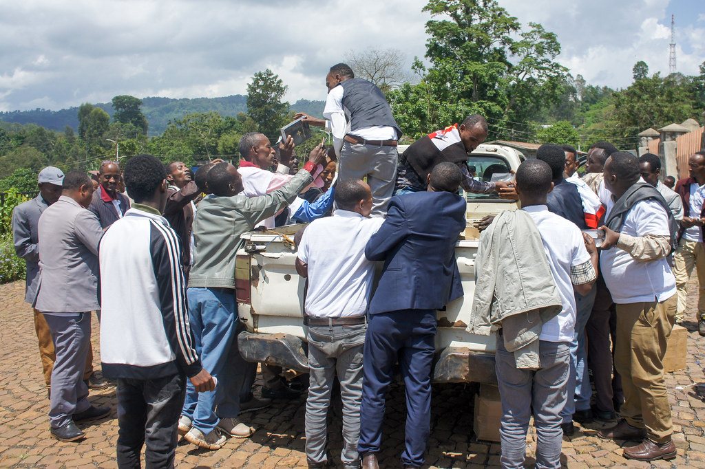 People crowding around truck to unload and purchase Kafa Bibles.