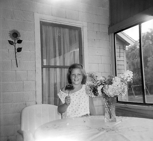 My first girlfriend holds a flower on our front porch. I really liked that off the shoulder look. We were both 8 years old and enjoyed rolling down Platt's Hill in my go-cart and playing