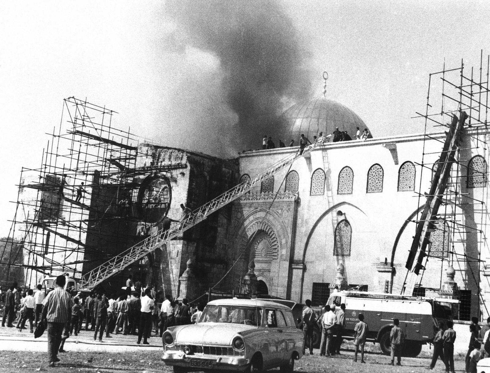 02. Толпа наблюдает за тем, как пожарные тушат пожар в мечети Аль-Акса. 21 августа