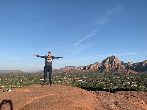 Author Shari Wallack standing on a rock, with arms spread wide. From Your Summer Must-Read: From Hell to Challah: Rising from Fragile to Fearless, One Grain at a Time