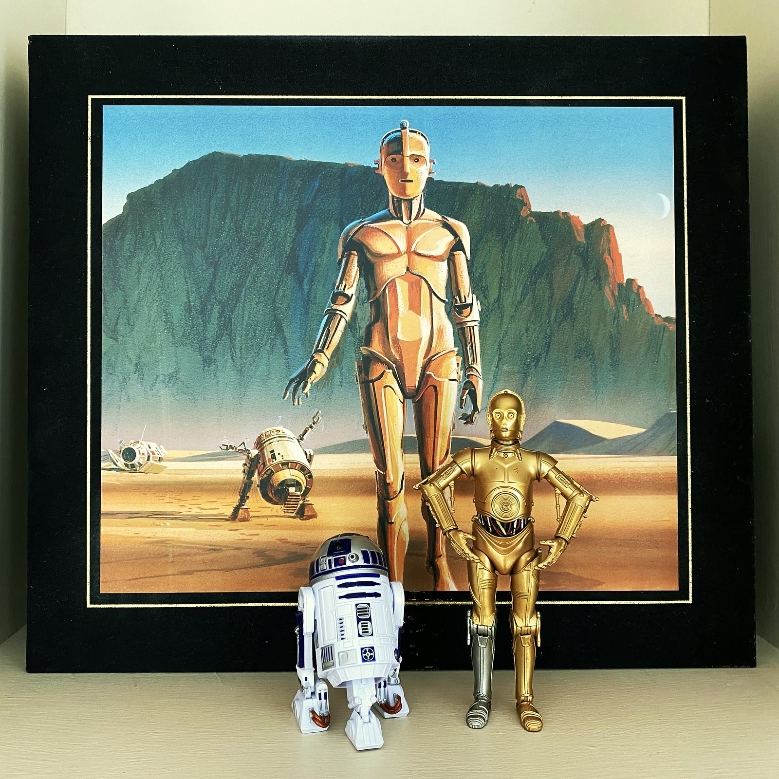 Models of R2D2 and C3PO stand in front of the cover of The Art Of Stars Wars book featuring early concept art of the two droids by Ralph McQuarrie