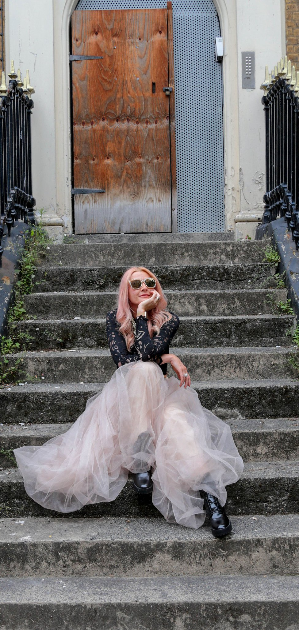Catherine Summers AKA Not Dressed As Lamb   Wearing: cropped, long sleeve black lace top, pearl-effect square sunglasses, nude tulle maxi skirt, black lace-up boots   Sitting on the steps leading up to a boarded-up abandoned London town house