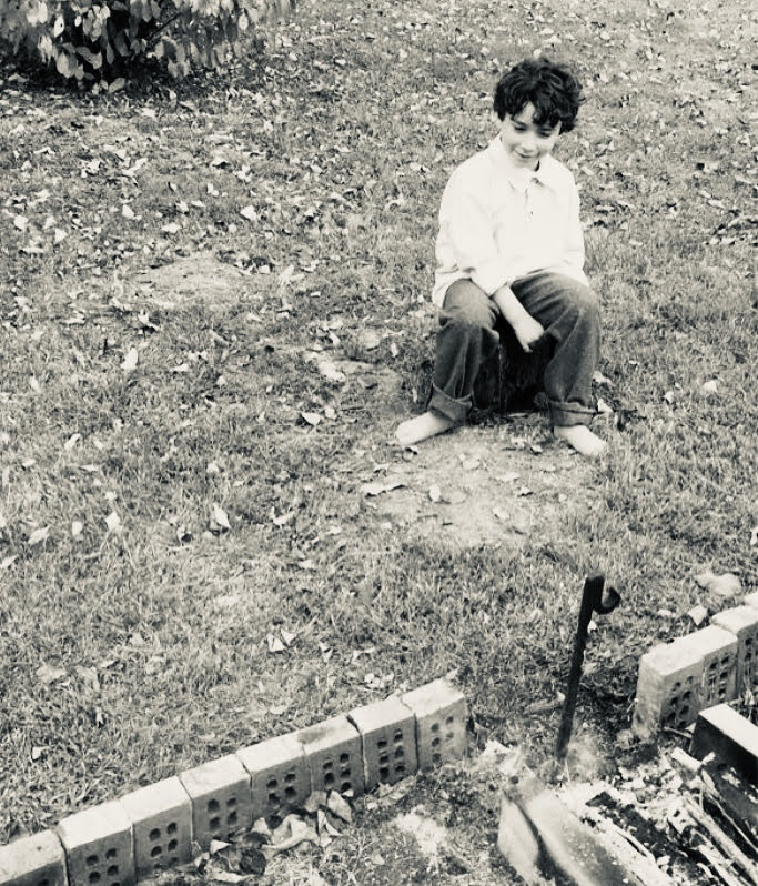 Boy Sitting by Outdoor Fireplace, 1870s
