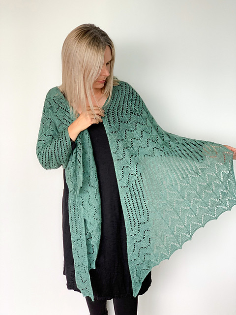 Helen Stewart's In The Dunes Wrap is a light and airy asymmetrical rectangle with flowing stripes of lace, designed and knit using The Fibre Co Meadow.