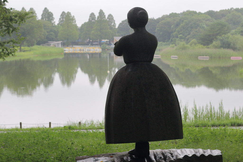 A Statue of  a Woman standing in front of  a park pond