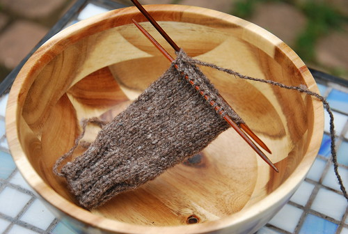 A handknit swatch of handspun Olde English Southdown cable yarn is a tube with ribbing at the cast-on edge and stockinette body. The yarn is on 2 double-point needles and is a medium brown with flecks of lighter coloured wool in a wooden bowl.
