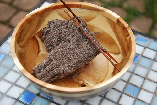 A handknit swatch of handspun Olde English Southdown cable yarn is on 2 double-point needles and has a 2x2 rib at the cast-on edge and a stockinette body forming a tube.  The knit swatch rests on a ball of the working yarn and both are a medium brown with flecks of lighter coloured wool in a wooden bowl.  The bowl sits on a blue and white mosaic table.