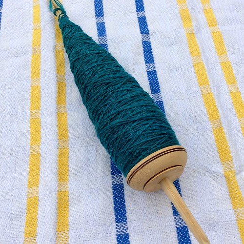 A medium CTTC pushka low-whorl drop spindle has a full cop of 3-ply Southdown/Silk yarn spun by irieknit that is a deep teal colour.  The spindle is shown on a handwoven twill tea towel with a white background and yellow and blue vertical stripes.