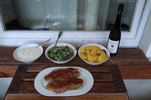 Paniertes Rotbarschfilet mit Gurkensalat, Salzkartoffeln und Joghurtsoße (Tischbild)